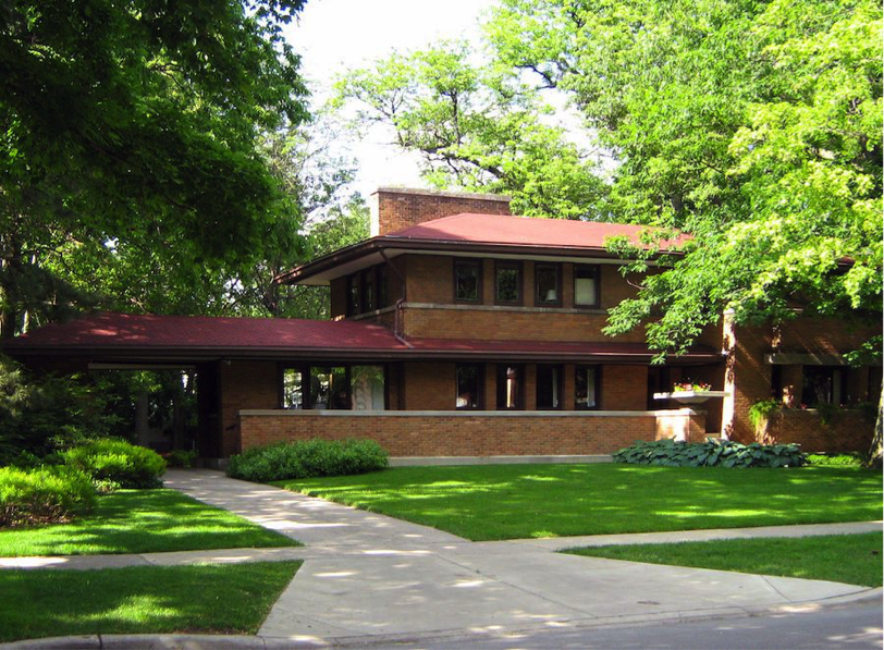 Description: The exterior of the Harry S. Adams house. The facade is red brick. The house is surrounded by trees.